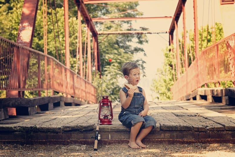 Boy eating sandwich taking break from fishing. Boy eating sandwich fishing bridge stock image
