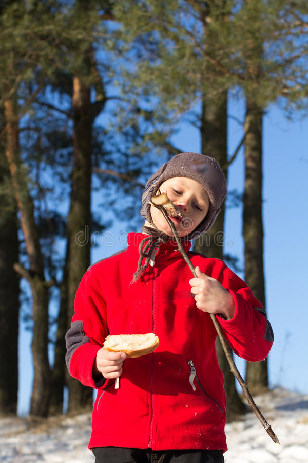 Boy eating shish kebab on nature in winter.  stock images
