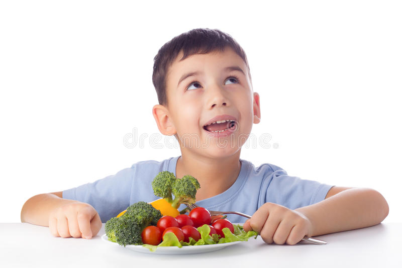 Boy eating vegetables. Happy child eating healthy vegetables royalty free stock image