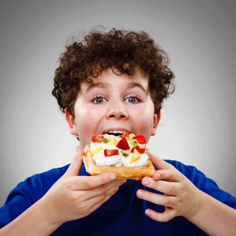 Boy eating waffle royalty free stock image