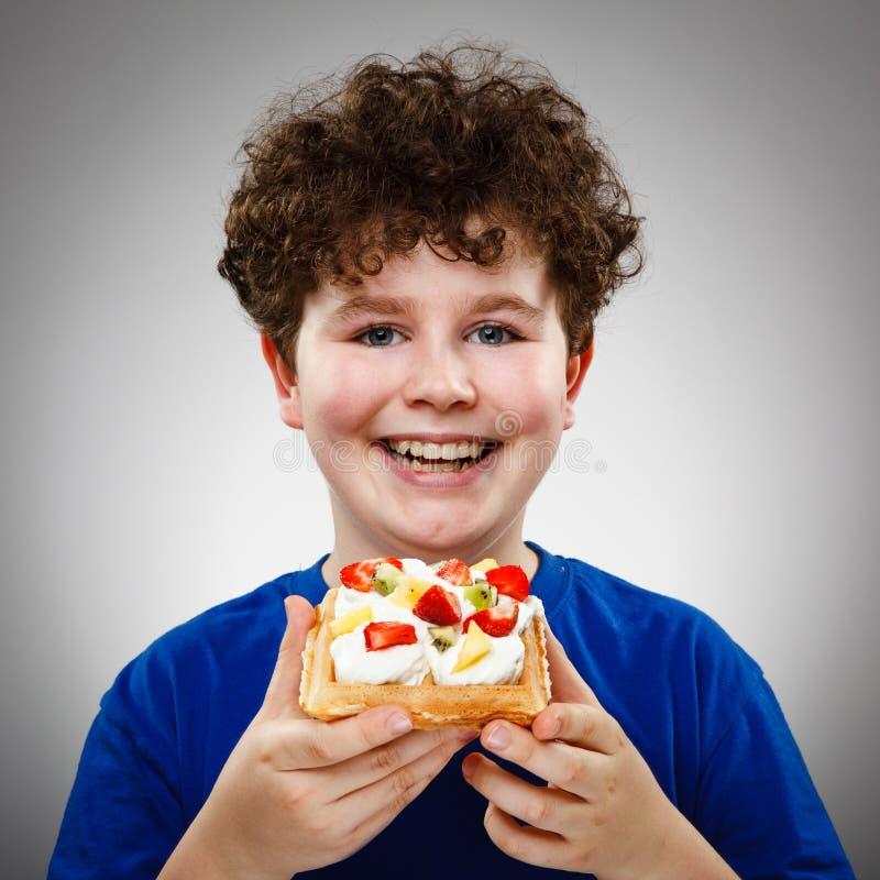 Boy eating waffle stock image