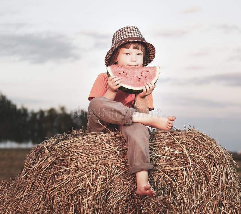 Boy eating watermelon stock photography