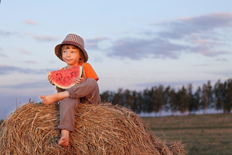 Boy eating watermelon outdoors royalty free stock photos