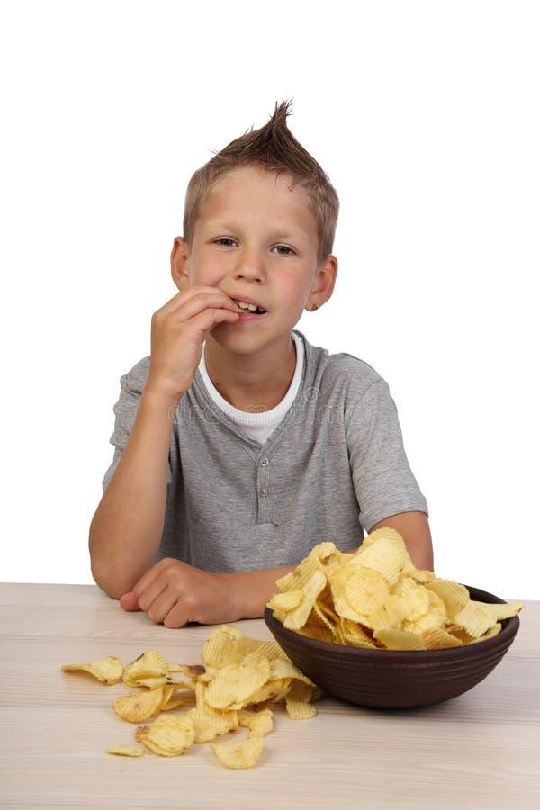 Boy eats chips stock photo