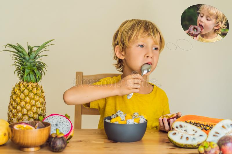 Boy eats fruit but dreams about donuts. Harmful and healthy food for children. Child eating healthy snack. Vegetarian royalty free stock images