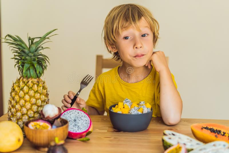 Boy eats fruit. Healthy food for children. Child eating healthy snack. Vegetarian nutrition for kids. Vitamins for royalty free stock photo