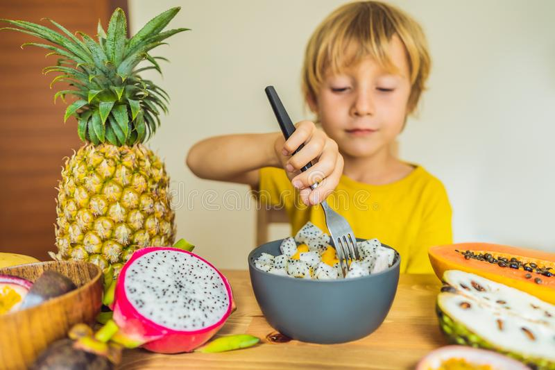 Boy eats fruit. Healthy food for children. Child eating healthy snack. Vegetarian nutrition for kids. Vitamins for stock photography