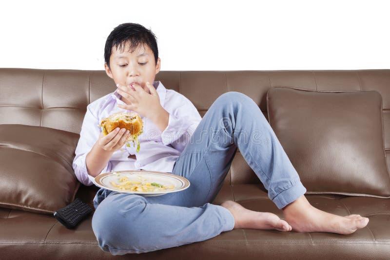 Boy eats hamburger on sofa royalty free stock images