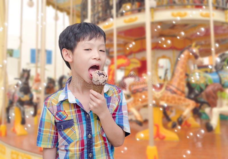 Boy eats icecream in front of merry go round. Young Asian boy eats icecream in front of merry go round royalty free stock photography