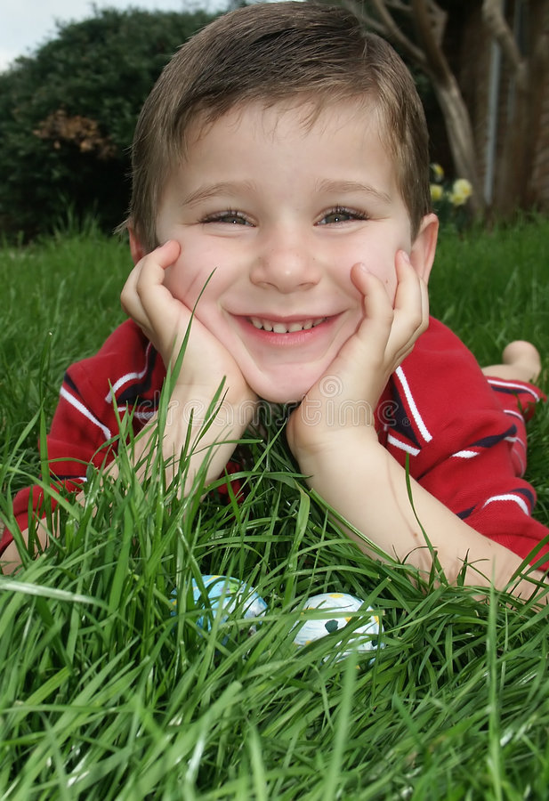 Boy with eggs 1. A young boy leaning in the grass and smiling about finding Easter eggs stock images