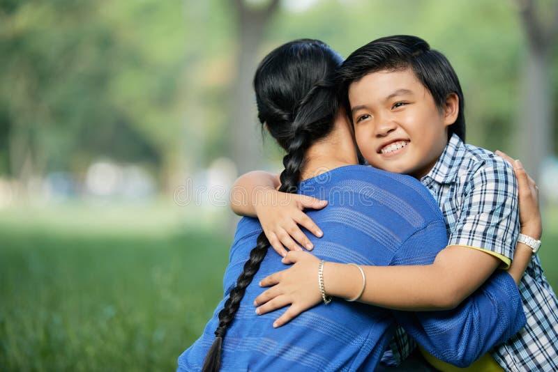 Boy embracing his mother. Joyful Vietnamese boy embracing his mother in city park royalty free stock images