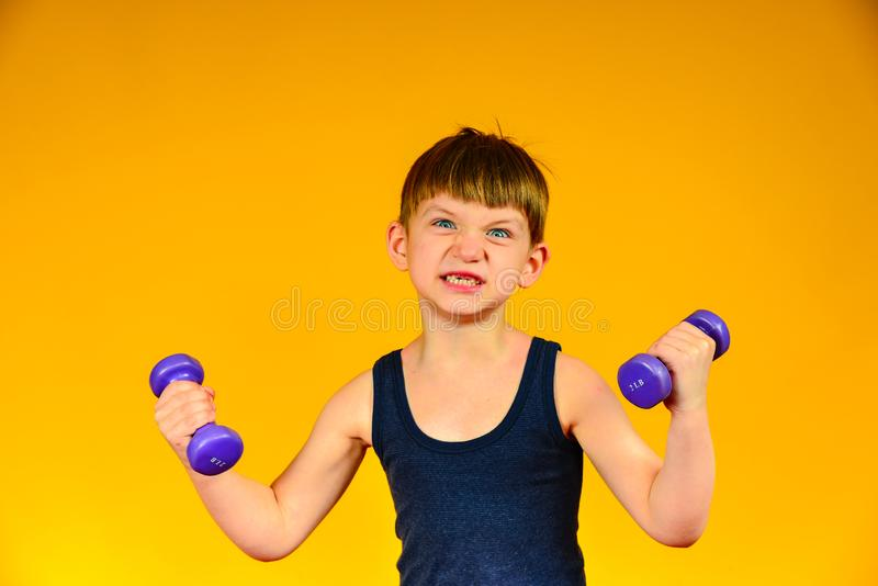 The boy is engaged in bodybuilding, sports at a young age, the child`s weightlifting stock image