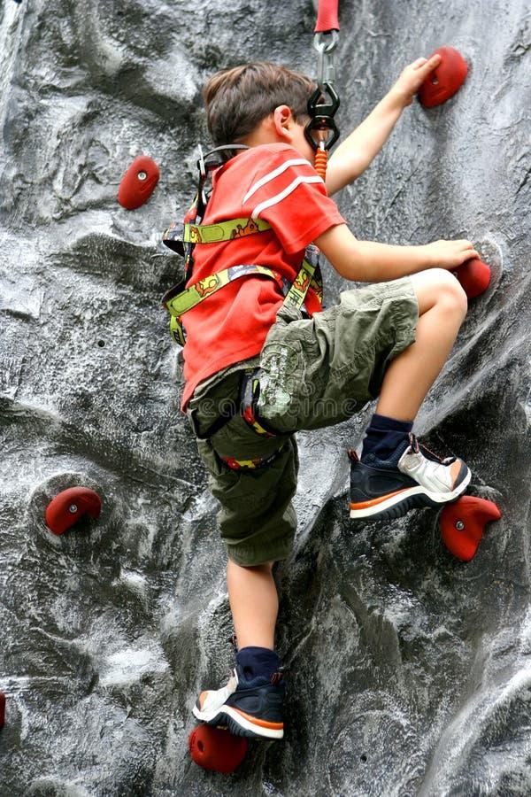 Boy enjoying rock climbing stock photography