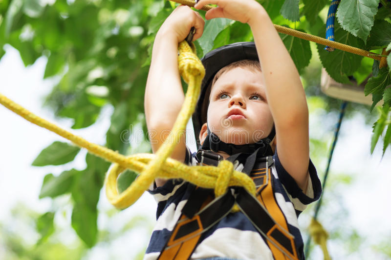 Boy enjoys climbing in the ropes course adventure. smiling child stock photos