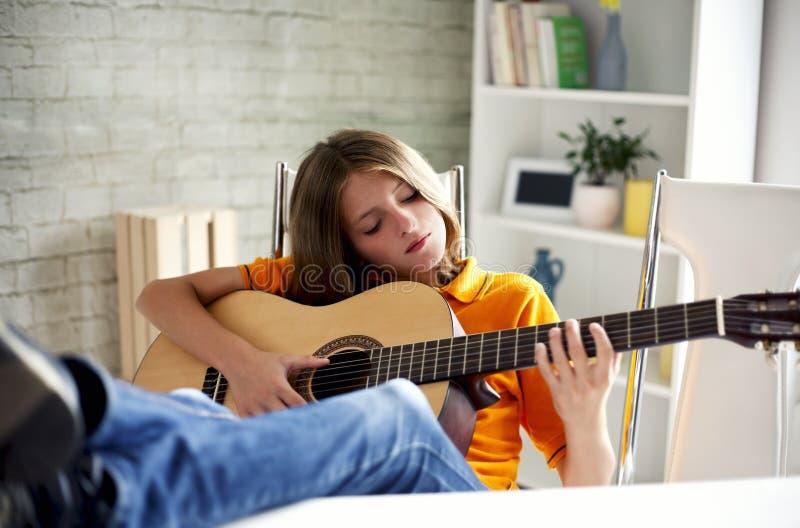 Boy enjoys playing the guitar stock photos