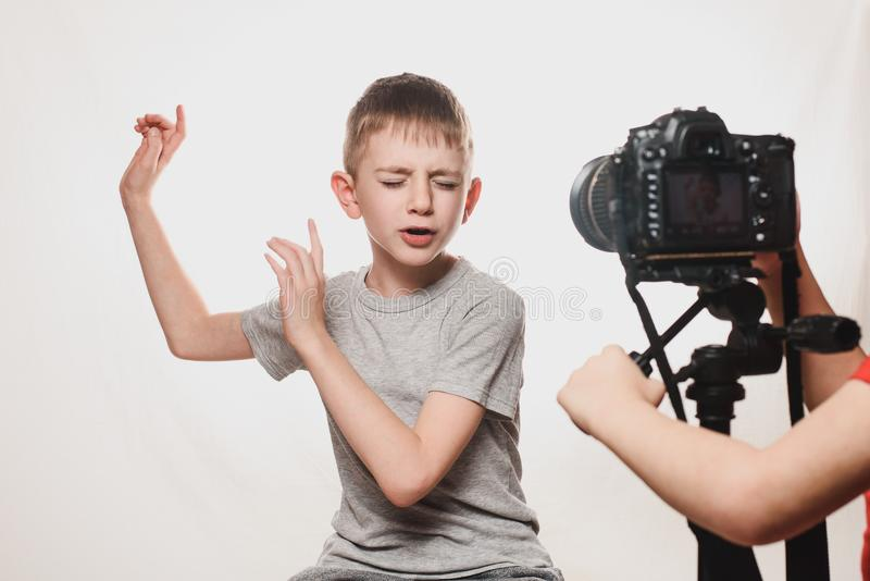 Boy enthusiastically sings in front of the camera. Children`s hands with a camera in the frame. Young video blogger. White stock image