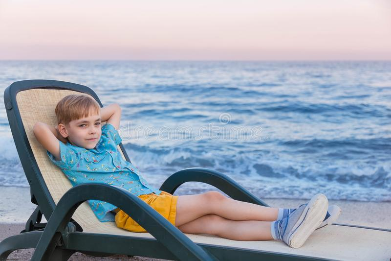 Boy of the European appearance in a blue striped t-shirt of a polo and yellow shorts has a rest in a chaise lounge at a surf strip. On the seashore at sunset royalty free stock image