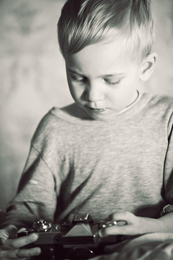 Boy examining retro camera with interest stock photos