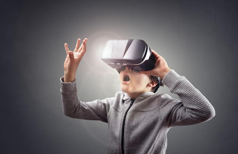 Boy experiencing using a virtual reality headset. Trying to touch something royalty free stock image