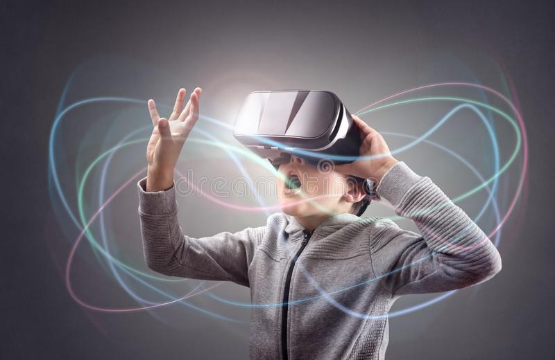 Boy experiencing using a virtual reality headset. Trying to touch something stock photography
