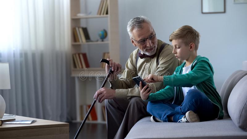 Boy explaining to old man how to use cell phone, simple technologies for old man stock photography