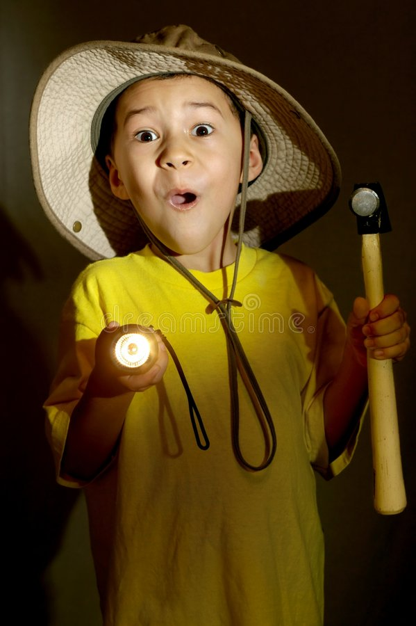 Boy exploring with flashlight. Seven-year-old boy exploring with a flashlight and hammer gets surprised shocked or frightened stock photos