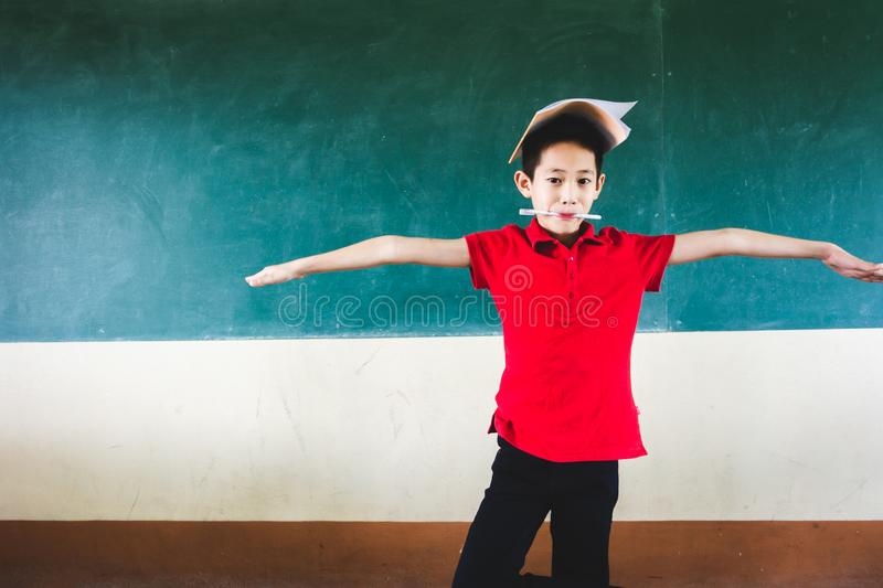 Boy extend the arms with book on head, standing before chalkboard, punishing stock photography