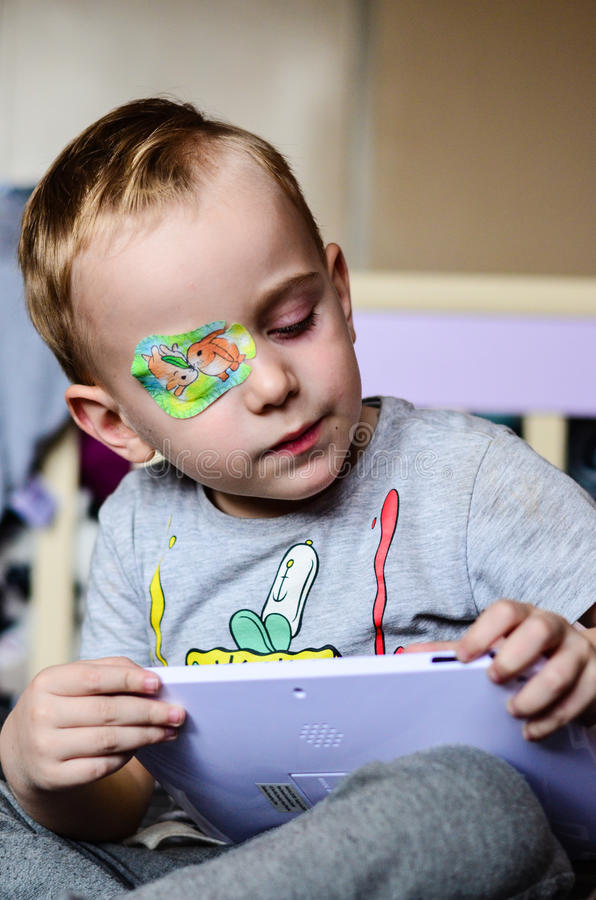 Boy with Eyepatch. Cute little boy with eyepatch for a correction of the vision playing on tablet royalty free stock photos