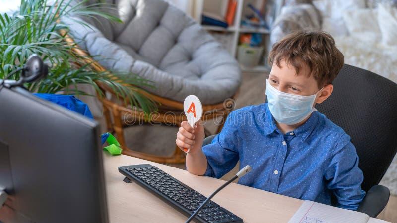 Boy in face mask using computer, doing homework during coronavirus quarantine. Boy in face mask with computer does his homework during a coronavirus quarantine royalty free stock image