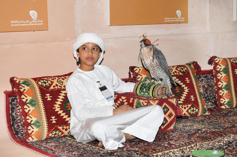 Boy with Falcon in Abu Dhabi International Hunting and Equestrian Exhibition (ADIHEX). Boy with Falcon oh his hand in Abu Dhabi International Hunting and royalty free stock images