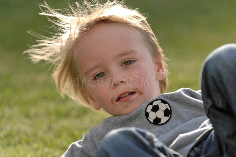 Boy falls playing football stock images