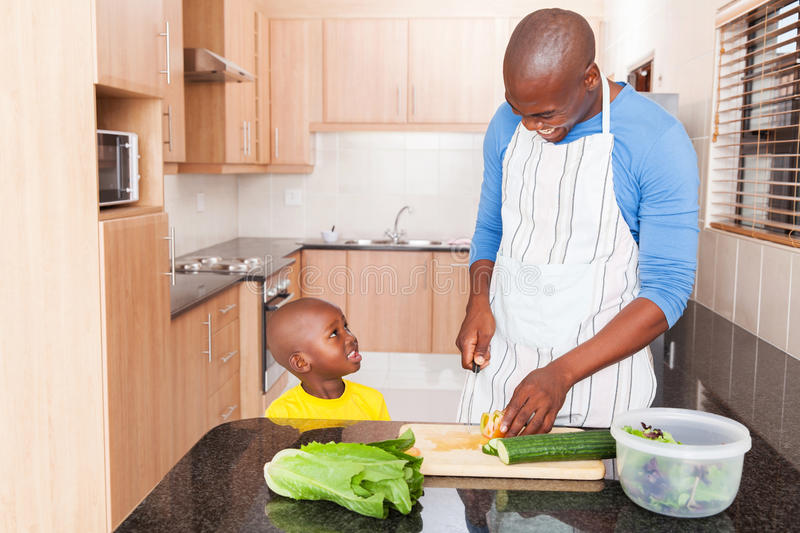 Boy father cooking. Adorable little african boy and his father cooking in kitchen royalty free stock photography