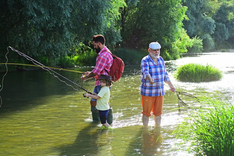 Boy with father and grandfather fly fishing outdoor over river background. Coming together. Father, son and grandfather. Fishing. Happy fathers day royalty free stock photo