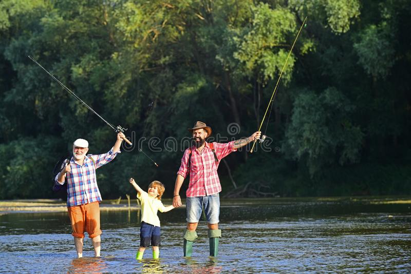 Boy with father and grandfather fly fishing outdoor over river background. Summer weekend. Happy fisherman with fishing royalty free stock photography
