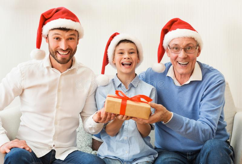 Boy, Father, Grandfather In Santa Hats Sitting On Couch Indoor stock photography