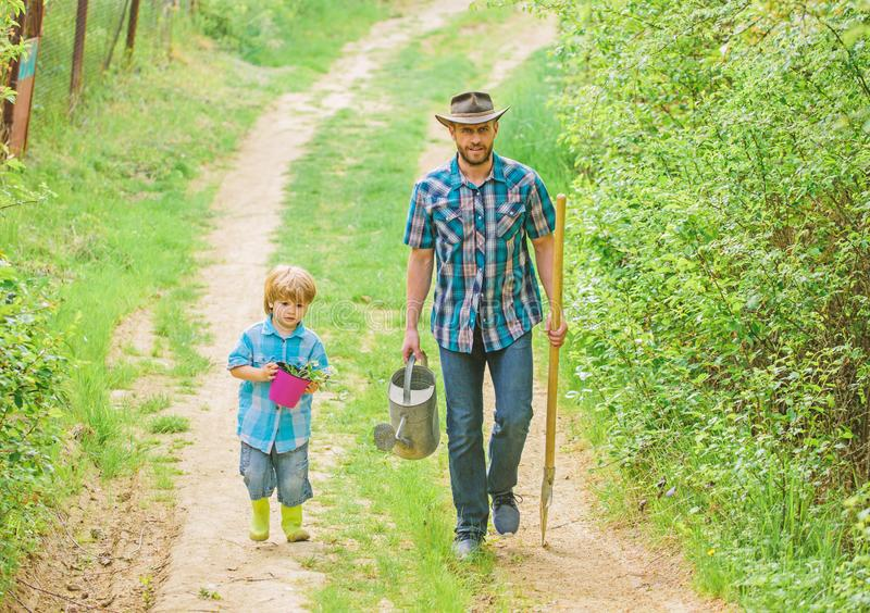 Boy and father in nature with watering can and shovel. Dad teaching son care plants. Arbor day. Planting trees. Tree. Planting tradition. Little helper in royalty free stock images