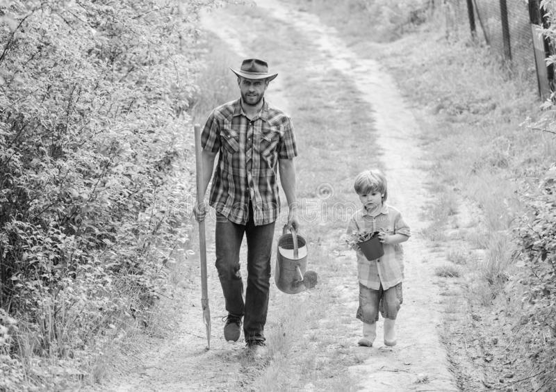 Boy and father in nature with watering can and shovel. Dad teaching son care plants. Arbor day. Planting trees. Tree. Planting tradition. Little helper in stock photos