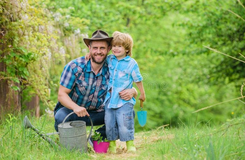 Boy and father in nature with watering can. Spring garden. Dad teaching little son care plants. Little helper in garden. Planting flowers. Growing plants royalty free stock photos