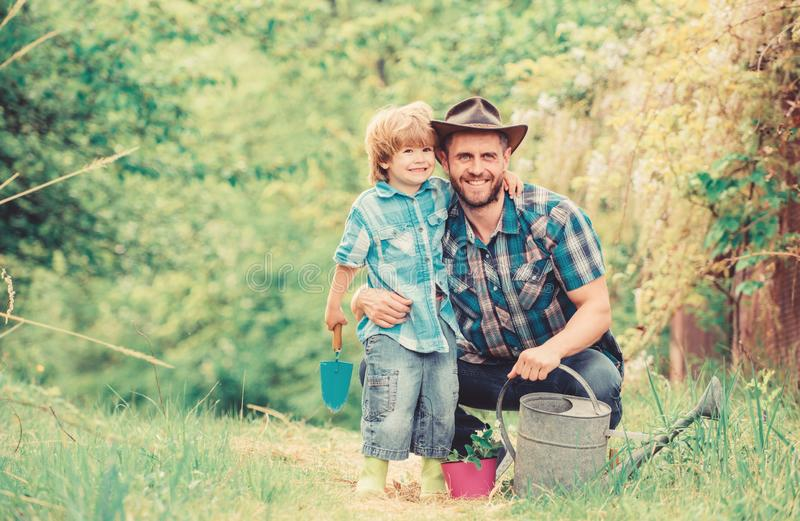 Boy and father in nature with watering can. Spring garden. Dad teaching little son care plants. Little helper in garden. Planting flowers. Growing plants royalty free stock images