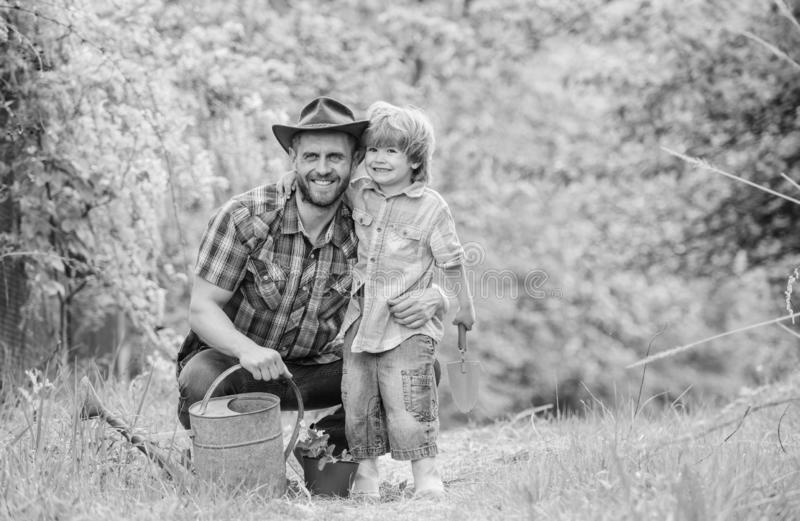 Boy and father in nature with watering can. Spring garden. Dad teaching little son care plants. Little helper in garden. Planting flowers. Growing plants royalty free stock image