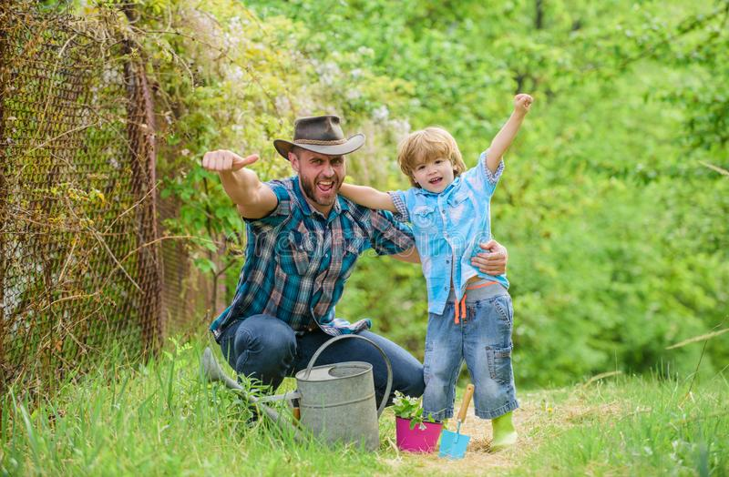Boy and father in nature with watering can. Spring garden. Dad teaching little son care plants. Personal example. Little. Helper in garden. Planting flowers stock photos