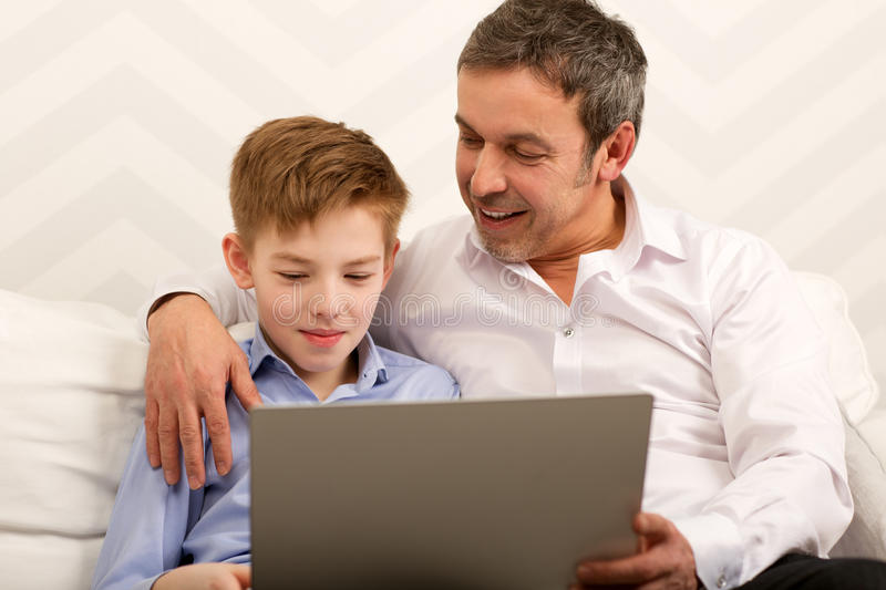 Boy and father using laptop together stock photos