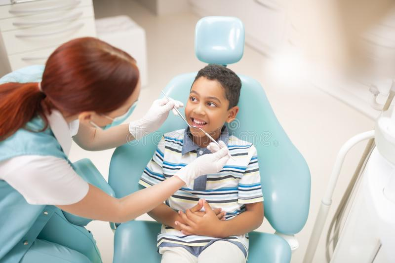 Boy feeling excited while having dental examination. Dental examination. Cheerful handsome boy feeling excited while having dental examination royalty free stock photography