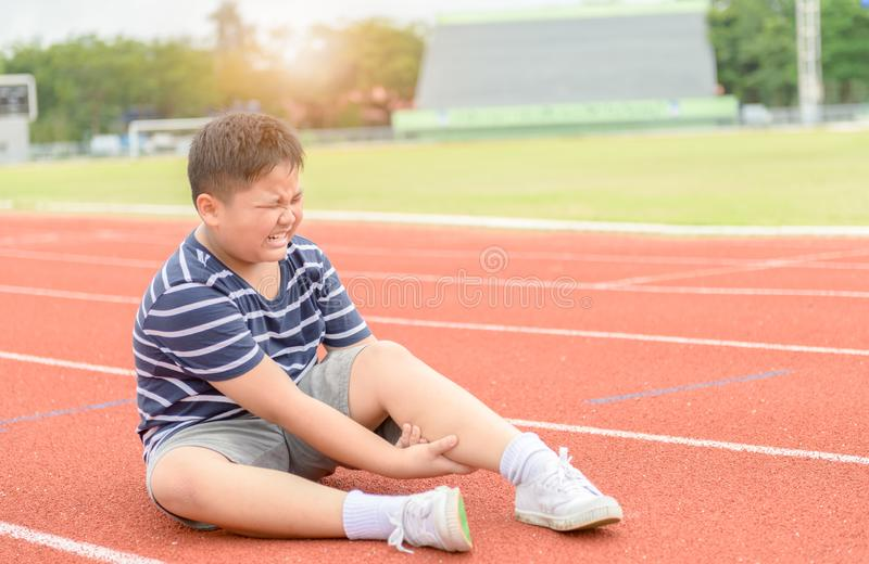 Boy feeling pain after having his calf pain. Obese boy feeling pain after having his calf pain on the track, Sport exercising injury concept stock photography