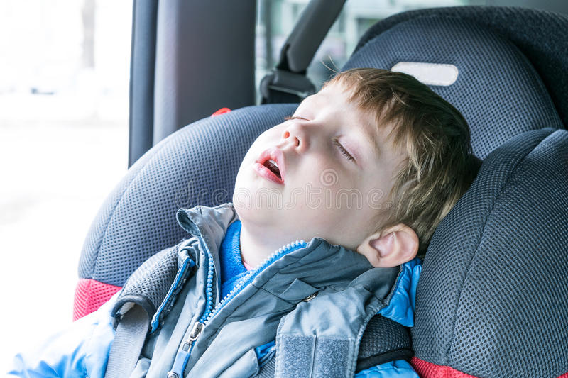 The boy fell asleep in the car child seat. Little boy sleeping in child car seat. The chair is very comfortable. A boy wearing a blue jacket and gray. Boy stock images