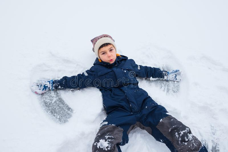 Boy fell in snow with his back, wants to make snow angel stock photo