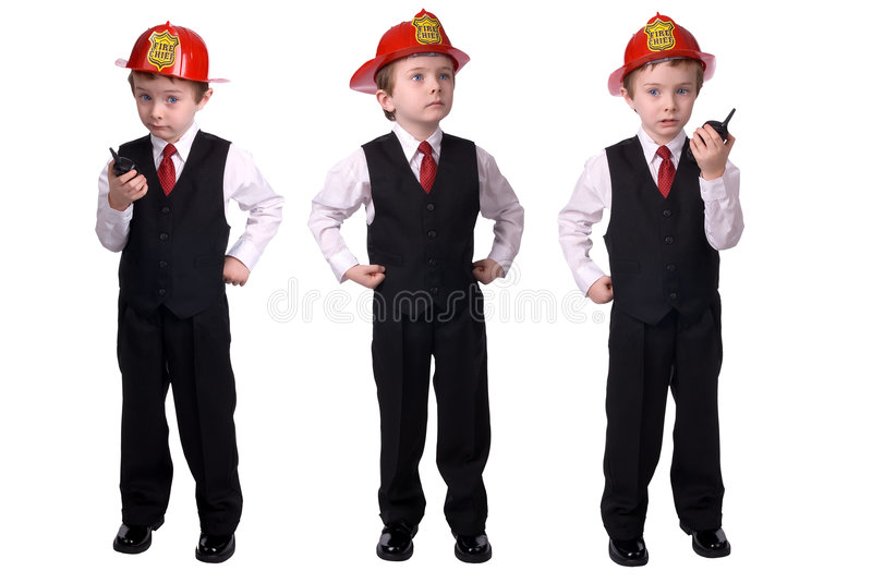 Boy Fire chief. Handsome attractive young boy dressed as a fire chief- in suit with helmet and walkie-talkie and hand on hip on white background royalty free stock image