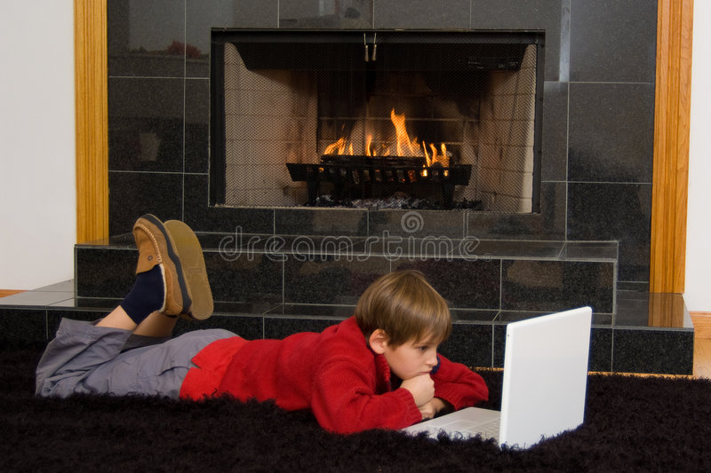 Boy at Fireplace on Computer. royalty free stock photography