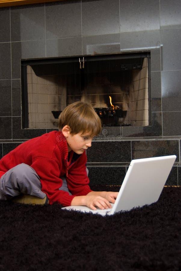 Boy at Fireplace on Computer. stock photos