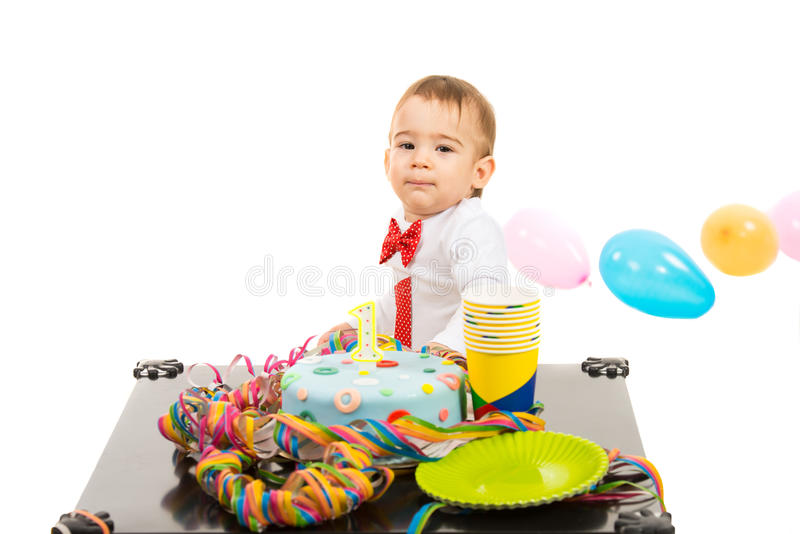 Boy at first anniversary. With colorful cake and balloons standing at table isolated on white background royalty free stock image